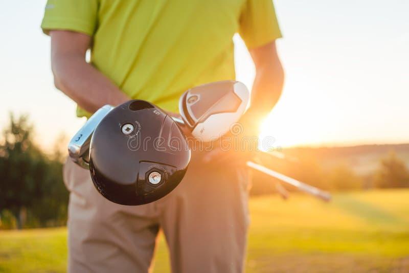 Zakończenie ręki samiec gracza mienia fachowi kije golfowi obraz stock