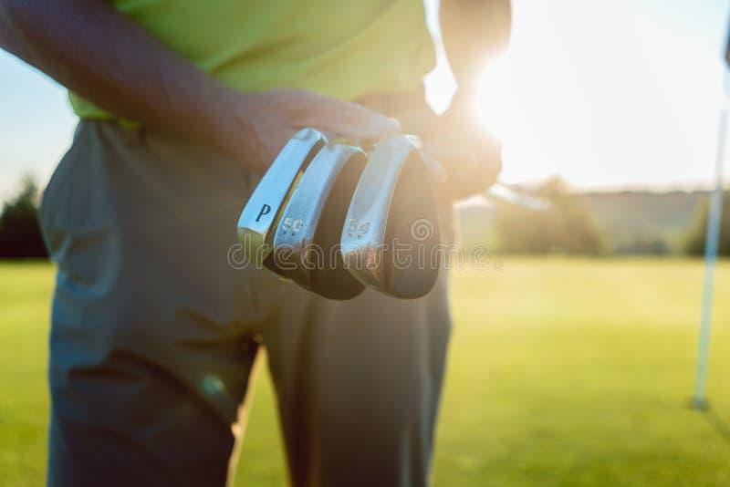 Zakończenie ręki samiec gracza mienia fachowi kije golfowi obrazy royalty free