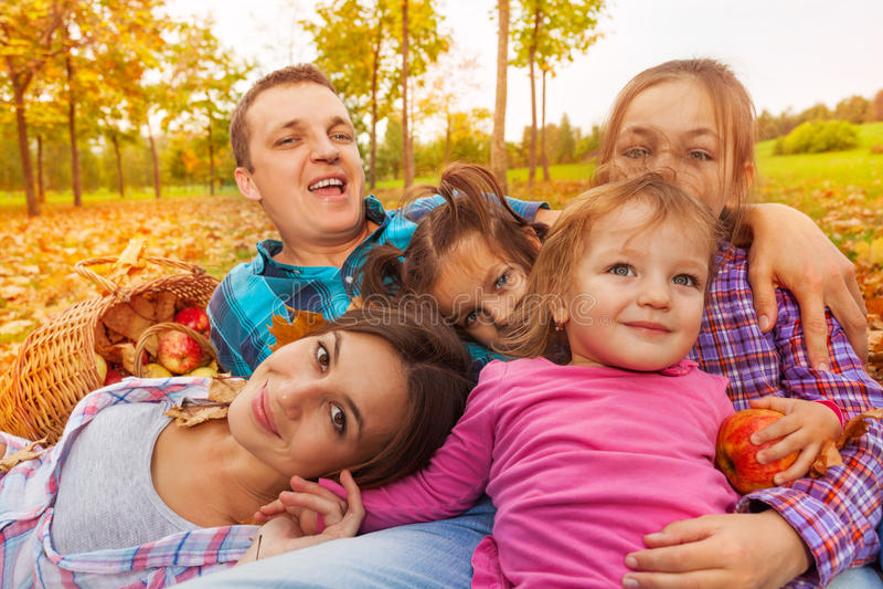 Zakończenie rodzina kłaść w jesień liściach zdjęcia stock
