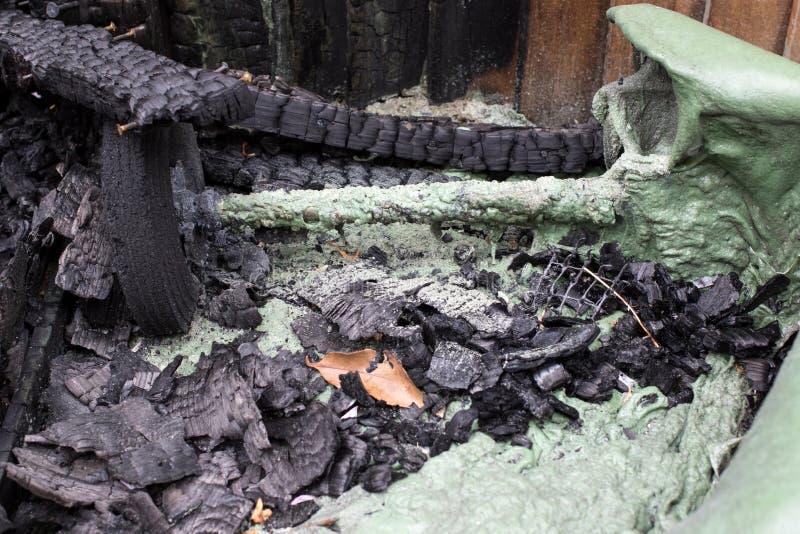 Zakończenie rozciekły zielony plastikowy wheelie kosz po ogienia zdjęcia stock