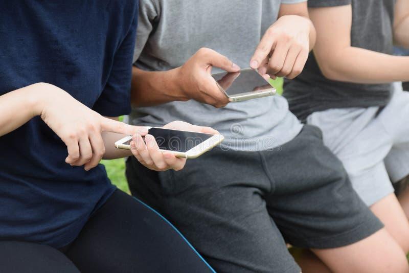 Zakończenie smartphones w rękach kobiety siedzi outdoors Spotkanie przyjaciele Dziewczyny używa cyfrowych gadżety obraz stock