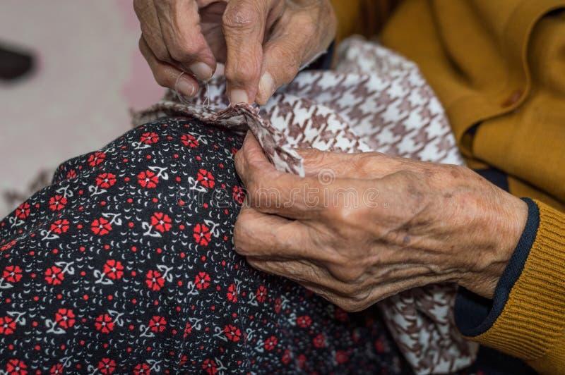 Zakończenie stara starsza kobieta up wręcza szyć fotografia royalty free