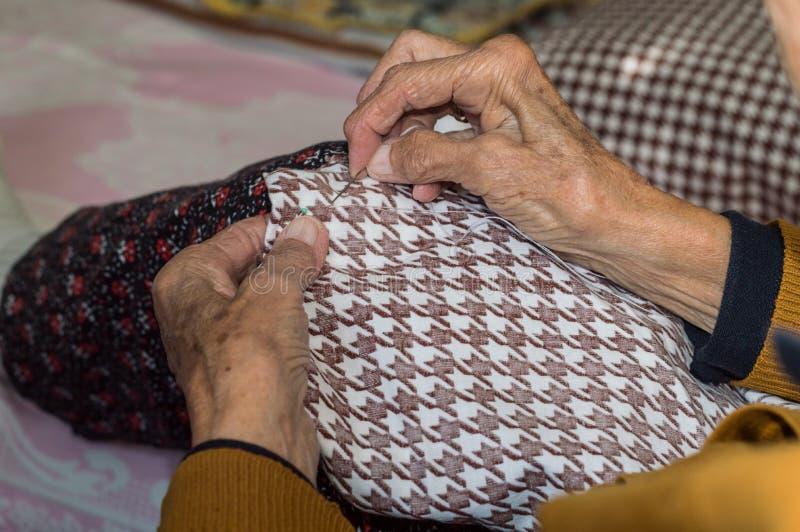Zakończenie stara starsza kobieta up wręcza szyć obraz royalty free