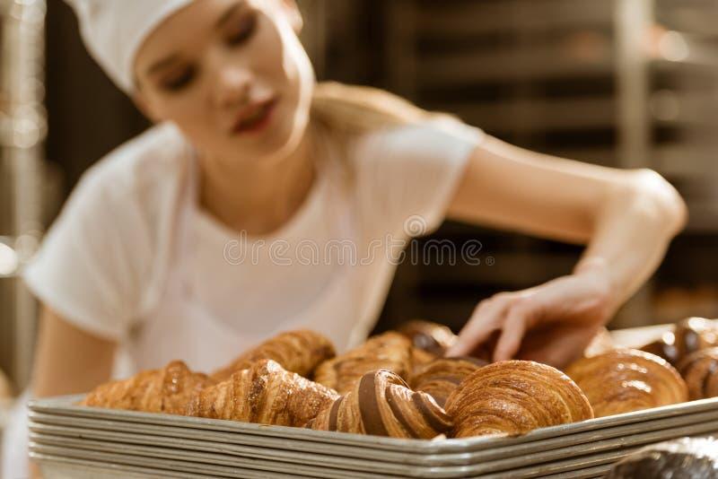 zakończenie strzał młody żeński piekarz robi egzaminowi świeżo piec croissants zdjęcie stock