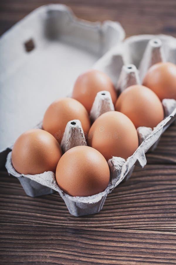 Zakończenie surowi kurczaków jajka w pudełku Jajka na starym drewnianym stole fotografia royalty free