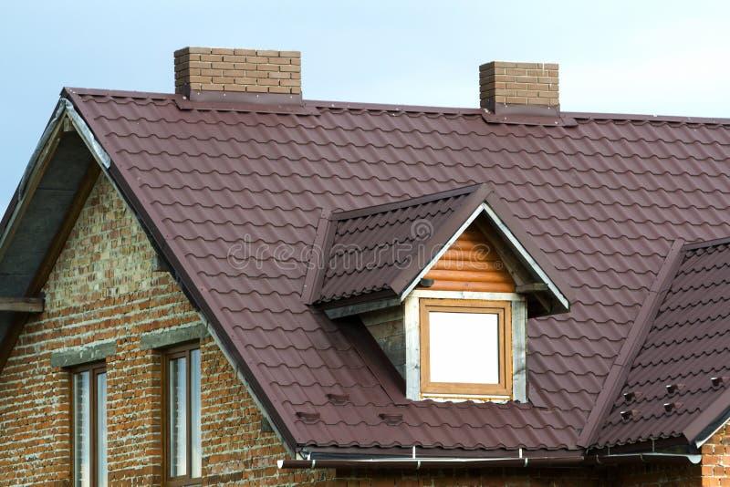 Zakończenie szczegół nowy cegła domu wierzchołek z brown gontu dachem, dwa ceglanymi kominami i plastikowymi strychowymi okno na  fotografia royalty free