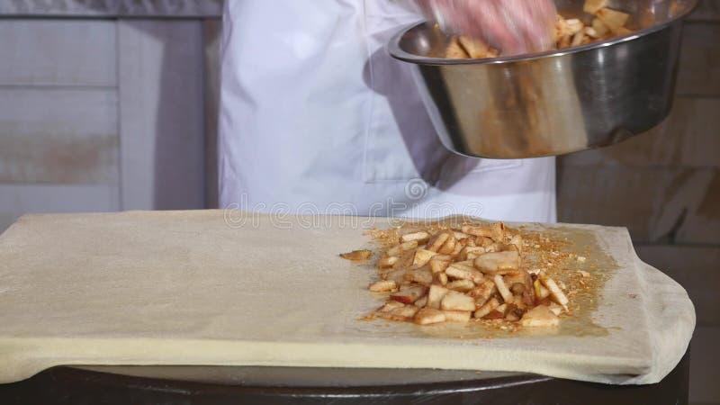 Zakończenie szef kuchni wręcza kładzenia jabłka kulebiak w restauracyjnej kuchni zdjęcie stock