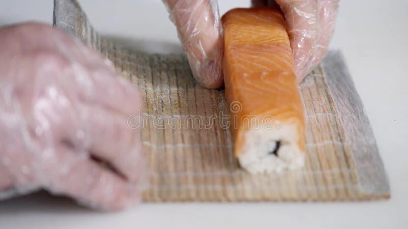 Zakończenie szef kuchni wręcza narządzaniu japońskiego karmowego robi suszi przy restauracją Potomstwa gotują słuzyć tradycyjnego obrazy royalty free