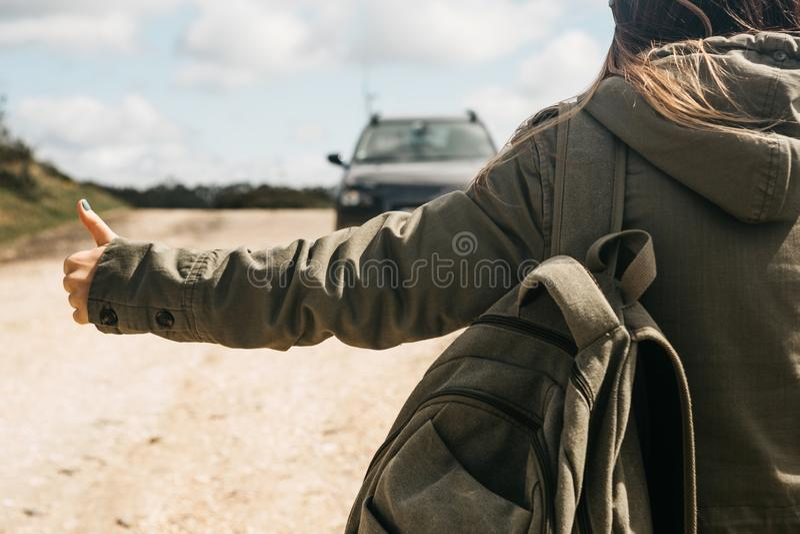 Zakończenie turystyczna dziewczyna z plecaka autostopem obrazy stock