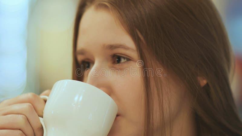 Zakończenie twarz młoda piękna uczennica, pije kawę od filiżanki fotografia stock