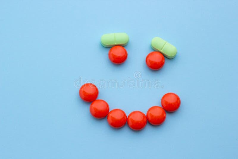Zakończenie, uśmiech od pomarańcze i zieleni pigułki, pojęć zdrowie zdjęcia stock