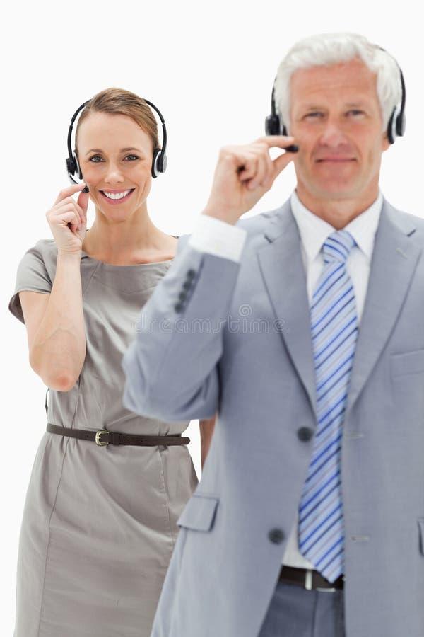 Zakończenie uśmiechnięta kobieta w tle i być ubranym słuchawki zdjęcie stock