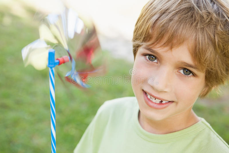 Zakończenie uśmiechnięty chłopiec mienia pinwheel w parku obrazy stock