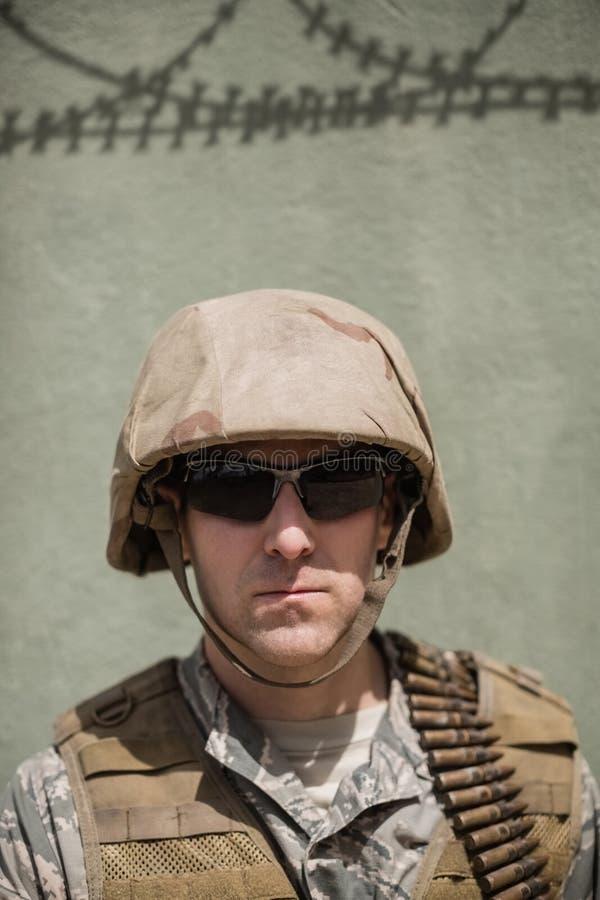 Zakończenie ufna militarna żołnierz pozycja przeciw betonowej ścianie zdjęcia stock