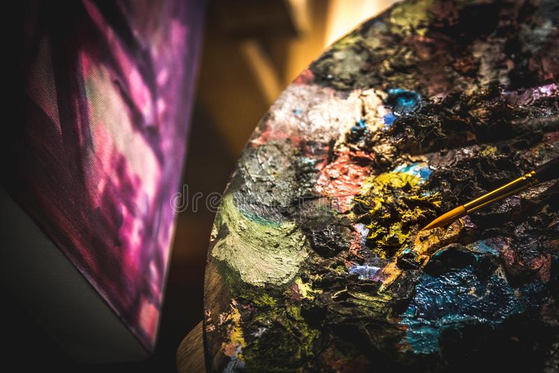 Zakończenie up artystów muśnięcia i nafciane farby na drewnianej palecie obrazy stock