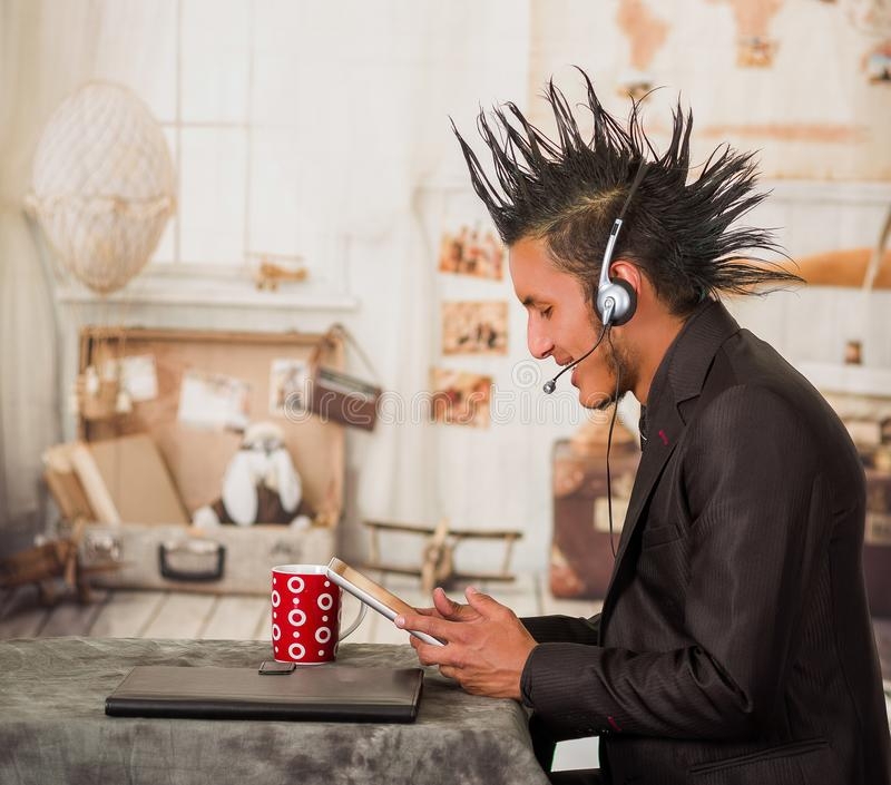 Zakończenie up biurowy punkowy mężczyzna, będący ubranym kostium z grzebienia włosianym stylem, używać jego hełmofony i pastylkę  obrazy stock