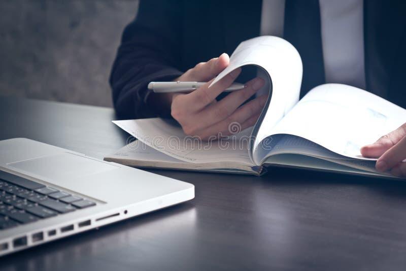 Zakończenie up biznesmen sprawdza dokumenty na biurowym biurku fotografia royalty free