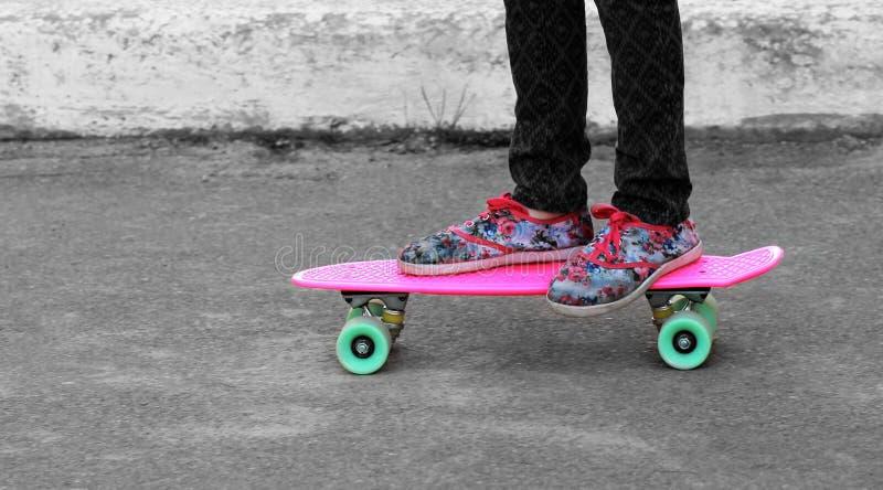Zakończenie up dziewczyny ` s cieki w kwiecistych sneakers stoi na różowej cent desce zdjęcia stock
