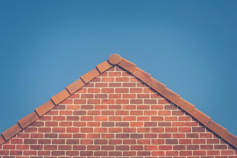 Zakończenie up kafelkowy dach na górze czerwonej cegły domu z niebieskim niebem w tle w rocznika stylu zdjęcia royalty free