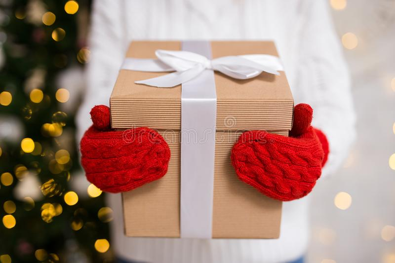 Zakończenie up kobiet ręki w rękawiczkach trzyma Bożenarodzeniowego prezenta pudełko zdjęcia stock