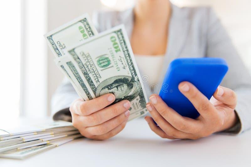 Zakończenie up kobiet ręki z smartphone i pieniądze obrazy royalty free