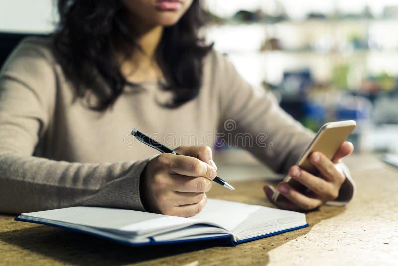 Zakończenie up kobiet ręki z telefonem i piórem zdjęcia royalty free