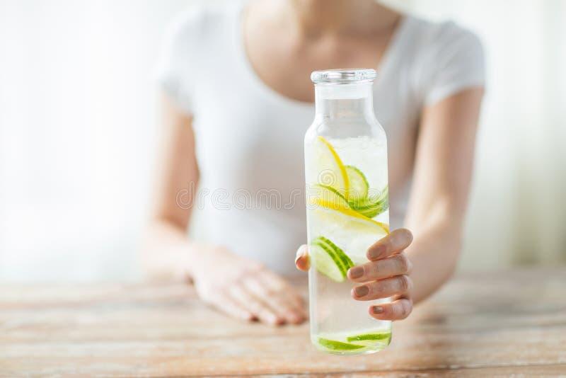 Zakończenie up kobieta z owoc wodą w szklanej butelce zdjęcia royalty free