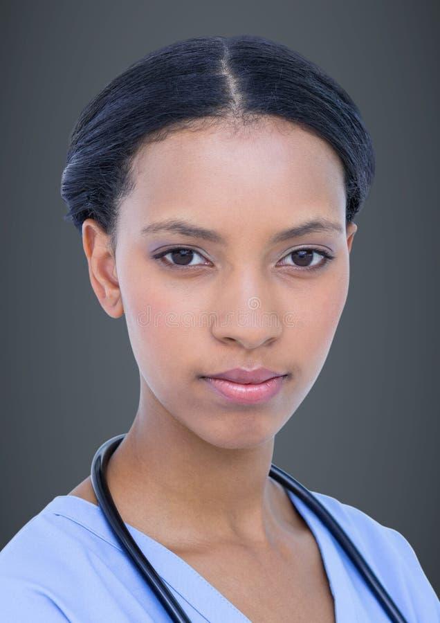 Zakończenie up kobiety lekarka przeciw popielatemu tłu fotografia stock
