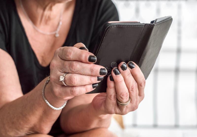 Zakończenie up kobiety stare ręki z czarnym gwoździa połysku mienia smartphone obraz royalty free