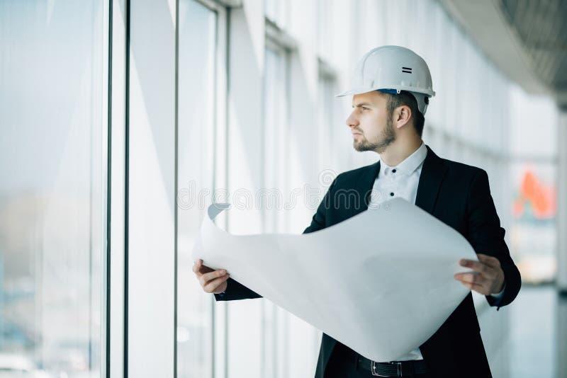 Zakończenie up konstruuje działanie na placu budowy trzymający projekt Inżynierii i architektury pojęcie zdjęcie royalty free
