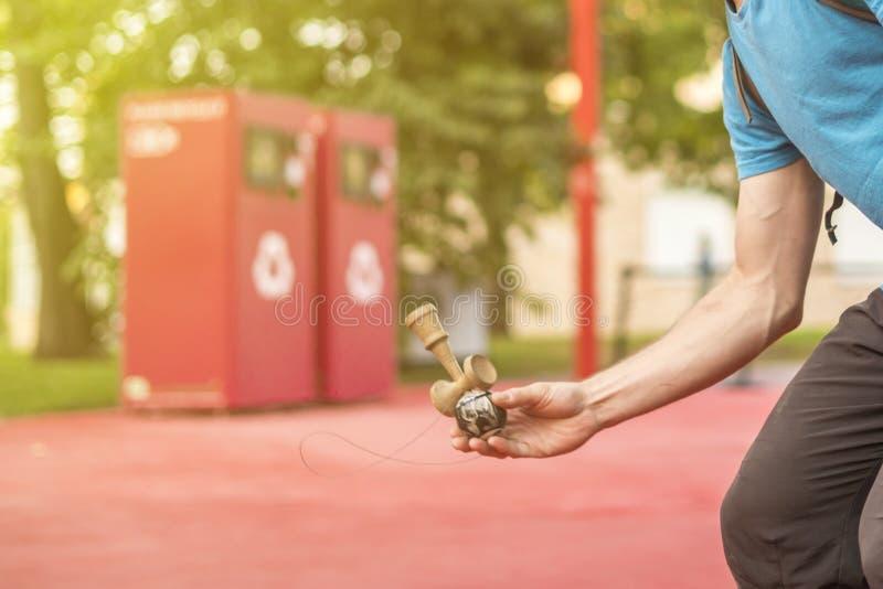 Zakończenie up mężczyzna wręcza robić sztuczkom z kendama w ulicie na letnim dniu fotografia royalty free