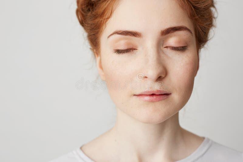 Zakończenie up młoda piękna rudzielec dziewczyna z zamkniętymi oczami nad białym tłem kosmos kopii fotografia royalty free