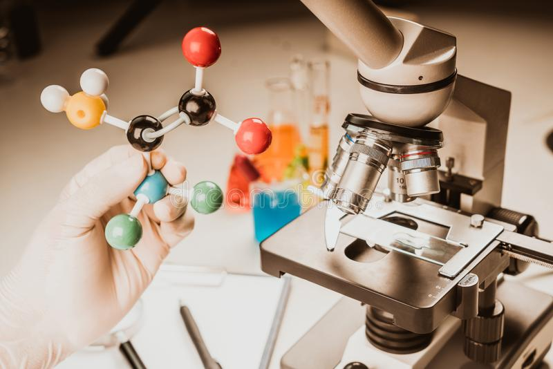 Zakończenie up mikroskopu viewing próbka z atom piłką i kija cząsteczkowym modelem dla badania, uczy się obrazy royalty free