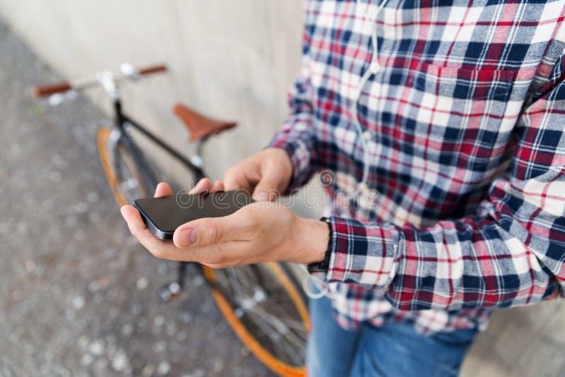 Zakończenie up modnisia mężczyzna z smartphone i rowerem zdjęcie stock