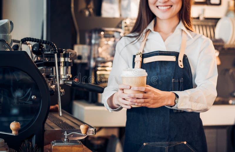 Zakończenie up na kawowym bierze oddaloną filiżankę z azjatykcim kobieta właściciela barista fotografia royalty free