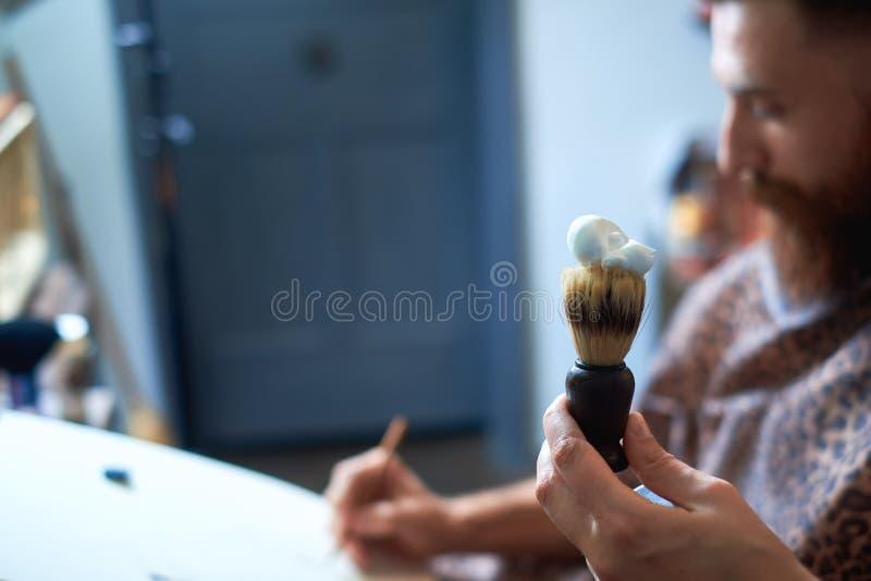 Zakończenie up pracuje dla atrakcyjnego młodego blondynu mężczyzna przy fryzjera męskiego sklepem hairdresses Robi tytułowaniu je zdjęcia royalty free