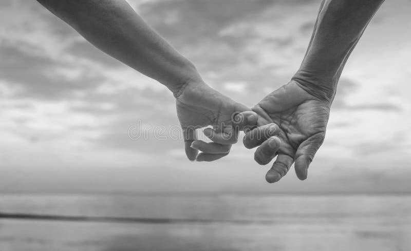 Zakończenie up ręka starszy para haczyk each other& x27; s mały palec wpólnie blisko nadmorski przy plażą, czarny i biały obrazek fotografia royalty free