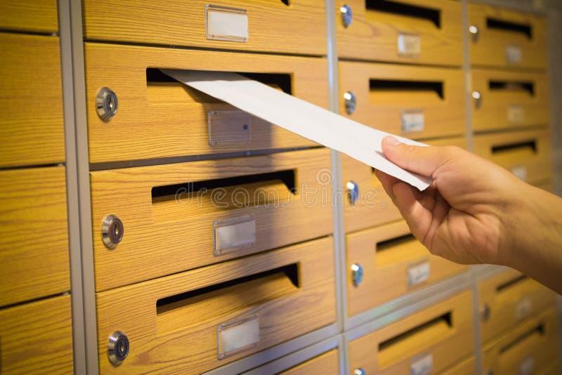 Zakończenie up ręka stawia żółtego list w skrzynkę pocztowa obrazy royalty free