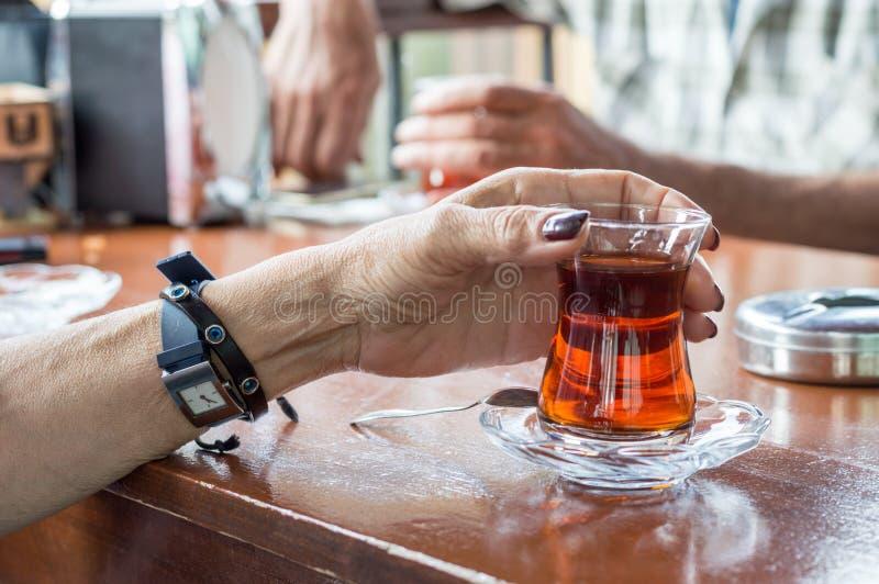 Zakończenie up starej kobiety ręka trzyma wyśmienicie czerwonej Tureckiej herbaty z tradycyjnym autentycznym szkłem na stole fotografia royalty free