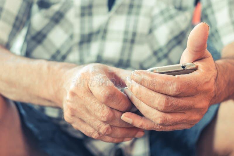 Zakończenie up starsza mężczyzna ręka używać mobilnego mądrze telefon obraz royalty free