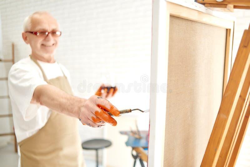 Zakończenie up starsza męska malarz ręka, malujący po raz ostatni uderzenie wewnątrz zdjęcie royalty free