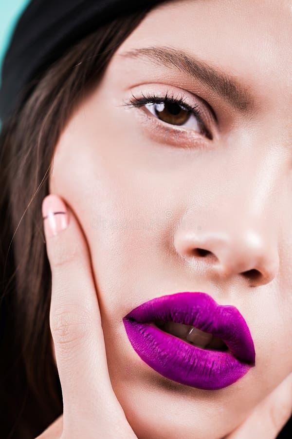 Zakończenie up twarz kobieta z profesjonalistą uzupełniał, purpurowe wargi, szczegół Moda piękna odosobniony portreta biel obraz stock