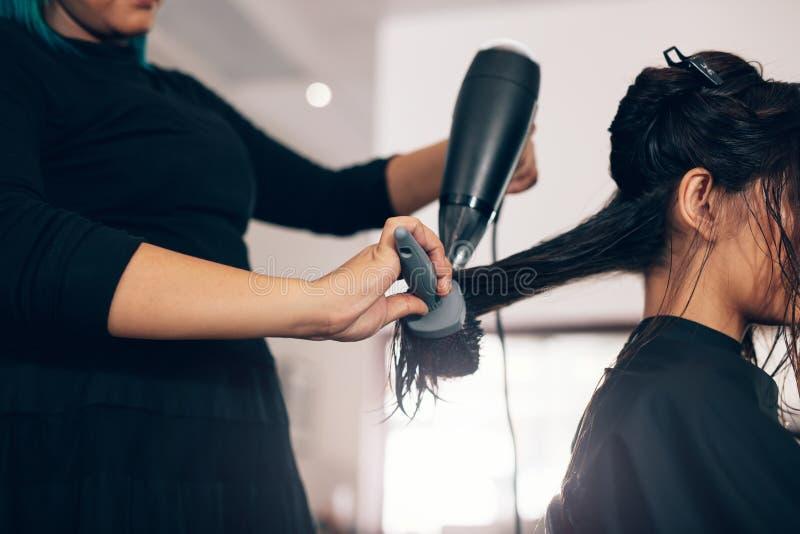 Zakończenie up włosiany stylista używa suszarkę na kobieta mokrym włosy w salonie obrazy royalty free