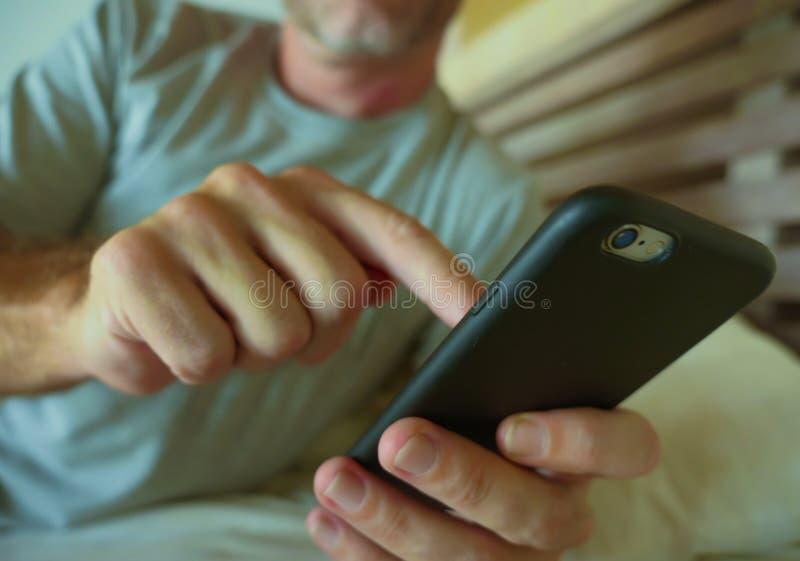 Zakończenie up wręcza mienie telefon komórkowego młody człowiek sypialnia w domu używać internetów ogólnospołecznych środki app n zdjęcia stock