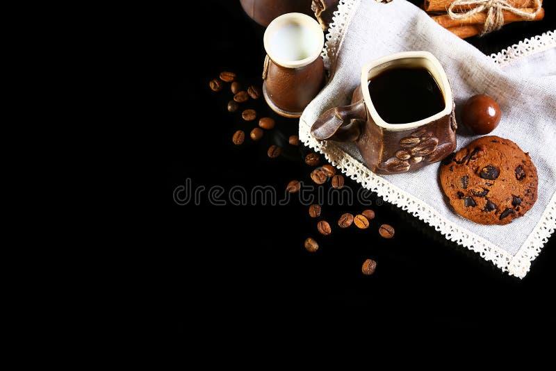 Zakończenie ustawiający kaw naczynia, kawy espresso kawa, mleko, round crunchy czekoladowi ciastka z kawowymi fasolami, kije cyna zdjęcie stock