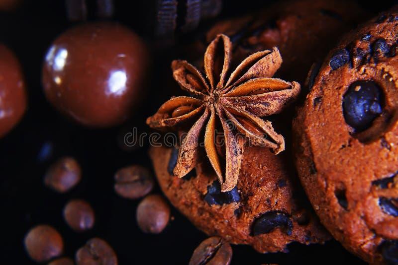 Zakończenie ustawiający round crunchy czekoladowi ciastka z kawowymi fasolami, anyż gwiazda na czarnym tle, makro-, set zdjęcie royalty free