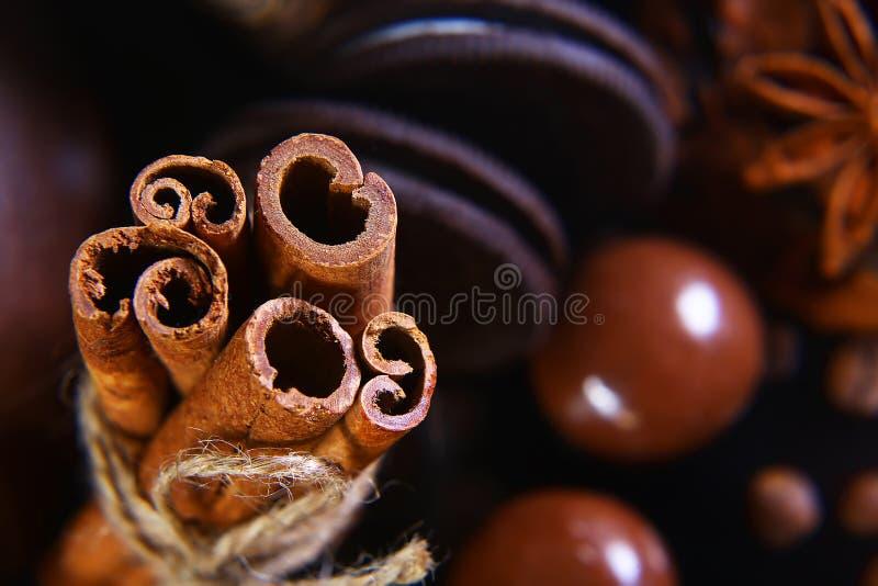 Zakończenie ustawiający round crunchy czekoladowi ciastka z kawowymi fasolami, kije cynamon, anyż gwiazda na czarnym tle, makro-, fotografia stock
