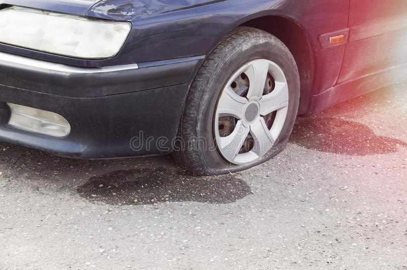 Zakończenie Uszkadzająca Płaska opona samochód Na drodze zdjęcie stock