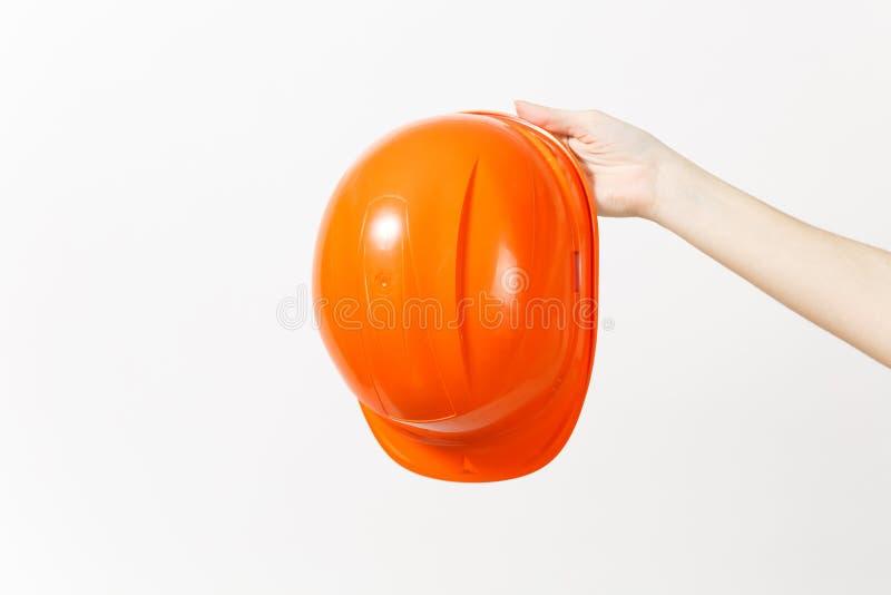 Zakończenie w górę żeńskiej ręka chwytów horyzontalnej ochronnej budowy pomarańczowego hełma odizolowywającego na białym tle inst zdjęcie royalty free