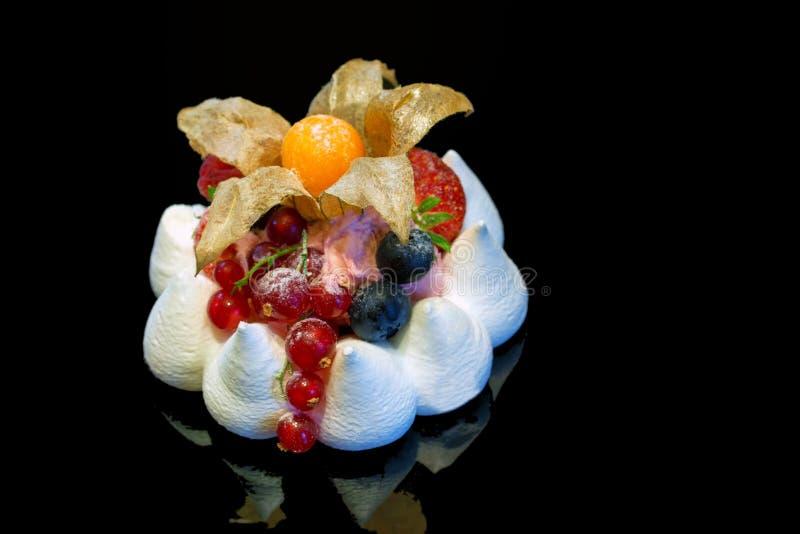 Zakończenie w górę beza torta z jagodami odizolowywać na darkbackground zdjęcia stock